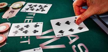 Pelipöytä, jolla mustia kortteja ja pelimerkkejä